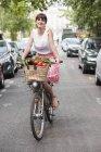 Retrato de mulher sorridente carregando legumes enquanto andava de bicicleta — Fotografia de Stock