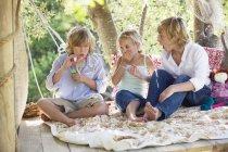 Crianças soprando varinha de bolha na casa da árvore — Fotografia de Stock