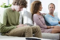 Niño usando el teléfono móvil mientras los padres hablan en segundo plano en la sala de estar en casa - foto de stock
