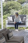 Happy woman relaxing on swing chair at porch and looking away — Stock Photo