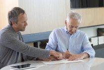 Старший занимается бумажной работой с финансовым консультантом дома — стоковое фото