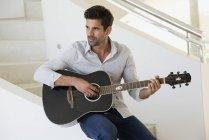 Впевнено людини грати на гітарі в домашніх умовах — стокове фото