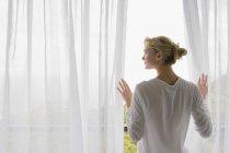 Vista trasera de la mujer de pie en el balcón y mirando a la vista - foto de stock