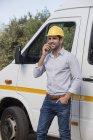 Ingenieur telefoniert vor Lieferwagen — Stockfoto