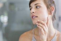 Jeune femme appliquant une crème hydratante sur les joues — Photo de stock