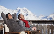 Young couple enjoying winter sun on wooden terrace in mountains — Stock Photo
