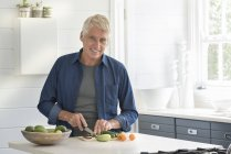 Счастливый пожилой человек готовит овощи на кухне и смотрит в камеру — стоковое фото
