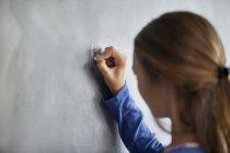 Primo piano di una ragazza adolescente che scrive sulla lavagna in classe — Foto stock