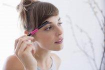 Nahaufnahme der jungen Frau, die Wimperntusche auftragen — Stockfoto