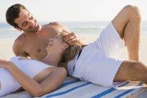 Расслабленная смеющаяся пара отдыхает на песчаном пляже — стоковое фото