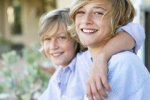 Портрет двух маленьких мальчиков, улыбающихся на улице — стоковое фото