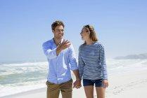 Couple heureux marchant sur la plage se tenant la main — Photo de stock