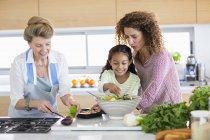 Старшая женщина с дочерью и внучкой готовят еду на кухне — стоковое фото