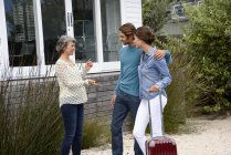 Happy mature woman meeting young couple with luggage outdoors — Stock Photo