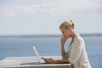 Mujer joven feliz usando teléfono inteligente en la mesa de madera con ordenador portátil en la orilla del lago - foto de stock