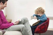 Веселий чоловік і син читають книжки вдома — стокове фото