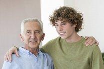 Retrato de homem idoso feliz abraçando neto adolescente — Fotografia de Stock