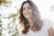 Крупный план счастливой женщины в солнечной природе — стоковое фото