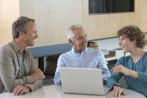 Heureux homme senior avec fils et petit-fils assis à table avec ordinateur portable dans le salon — Photo de stock