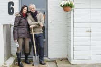 Couple standing at doorway of countryside house with shovel — Stock Photo
