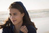 Молодая женщина в капюшоне отводит взгляд на пляже — стоковое фото