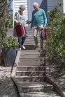 Felice coppia anziana portando valigie sulle scale — Foto stock