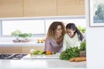 Young woman with daughter standing and talking in kitchen — Stock Photo
