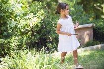 Маленькая девочка в летнем белом платье прогулка в летнем саду — стоковое фото