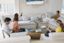 Multi-generation family using gadgets in living room — Stock Photo