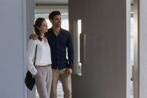 Sorrindo casal de pé à porta da casa e olhando para longe — Fotografia de Stock