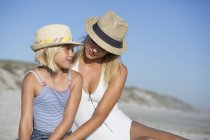 Blond young woman and daughter in hats sitting on beach — Stock Photo
