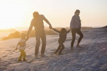 Parents with children walking on beach holding hands at sunset — Stock Photo