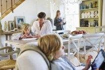 Мужчина обучает маленького мальчика дома с семьей на заднем плане — стоковое фото