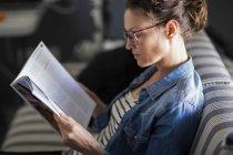 Primo piano della rivista di lettura donna pensosa mentre si siede sul divano — Foto stock