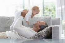 Happy father lying on sofa and playing with cute baby daughter at home — Stock Photo
