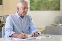 Homem sênior usando calculadora ao fazer papelada em casa — Fotografia de Stock