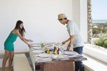 Sorridente giovane coppia organizzare cibo sul tavolo da pranzo — Foto stock