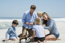 Happy family playing in sand on beach — Stock Photo