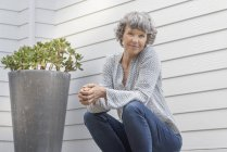 Mujer madura feliz sentado al lado de la planta en maceta en frente de la pared de la casa - foto de stock