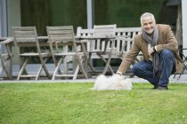 Smiling mature man playing with dog in garden — Stock Photo