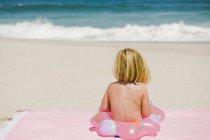 Маленькая девочка сидит с надувным кольцом на песчаном пляже — стоковое фото