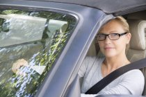 Close-up of smiling woman wearing eyeglasses driving a car — Stock Photo