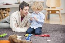 Людина грає з маленьким сином на килимі будинку — стокове фото