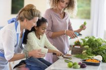 Senior woman with daughter and granddaughter in kitchen — Stock Photo