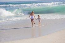 Donna che corre sulla spiaggia di sabbia con figlia — Foto stock