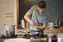Человек готовит еду на современной кухне — стоковое фото