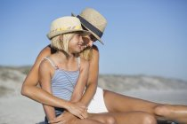 Smiling woman and daughter in hats sitting on sandy beach — Stock Photo