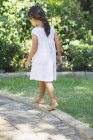 Rear view of little girl in white summer dress walking in sunny garden — Stock Photo