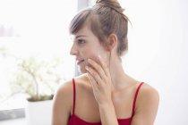 Giovane donna che applica idratante sul viso in bagno — Foto stock