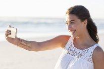 Feliz joven mujer tomando selfie con teléfono inteligente en la playa - foto de stock
